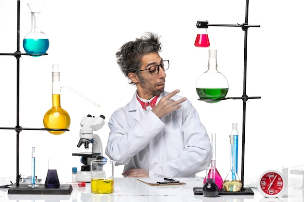 Vue de face chimiste d'âge moyen en costume médical blanc assis avec des solutions fixant son costume