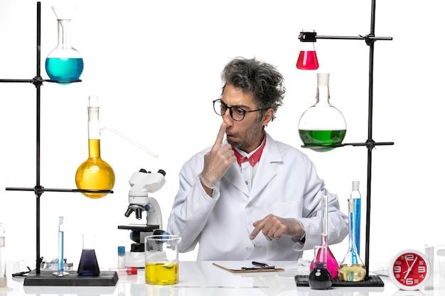 Vue de face chimiste d'âge moyen en costume médical blanc assis avec des solutions