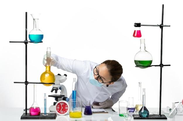 Vue de face chimiste en combinaison médicale avec masque travaillant avec des solutions sur fond blanc laboratoire de chimie de virus covid splash