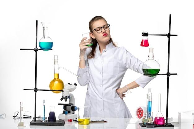 Vue de face chimiste en combinaison médicale en processus de travail avec des solutions sur fond blanc clair chimie virus covid pandémique