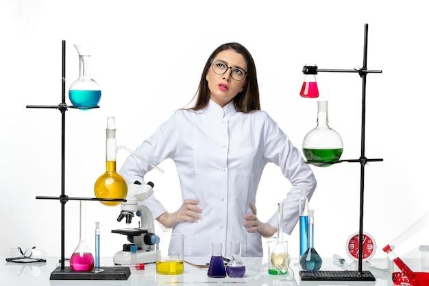 Vue de face chimiste en combinaison médicale stérile debout et pensant sur fond blanc maladie virale covid- science pandémique