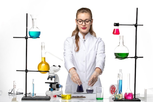 Vue de face chimiste en combinaison médicale travaillant avec différentes solutions sur le virus de la pandémie pandémique de chimie de bureau blanc-