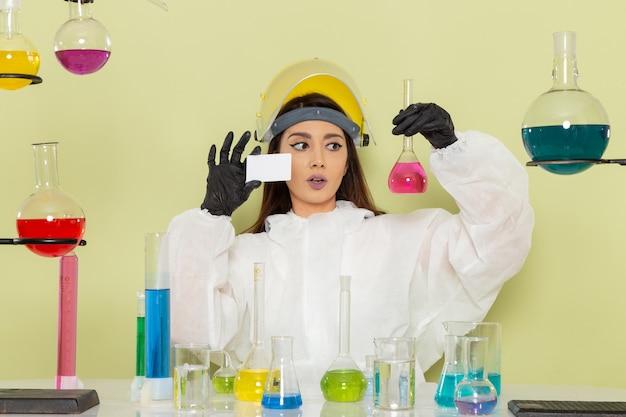 Vue de face chimiste en combinaison de protection spéciale travaillant avec une solution sur une surface vert clair