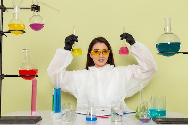 Vue de face chimiste en combinaison de protection spéciale travaillant avec des solutions et souriant sur une surface verte