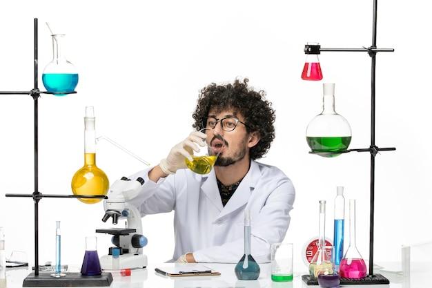 Vue de face chimiste masculin en combinaison médicale solution potable sur espace blanc