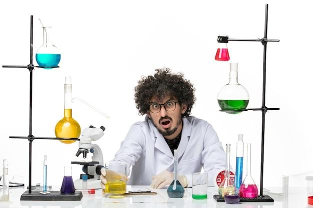 Vue de face chimiste masculin en combinaison médicale tenant une solution sur un espace blanc