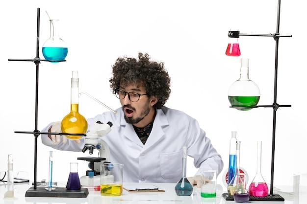 Vue de face chimiste masculin en costume médical à l'aide d'un microscope sur un bureau blanc