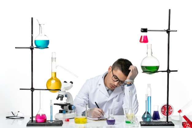 Vue de face chimiste masculin en costume médical assis et écrit quelque chose sur fond blanc virus covid splash maladie science