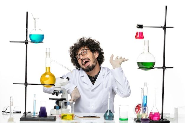 Vue de face chimiste masculin en costume médical assis et faisant des grimaces sur l'espace blanc