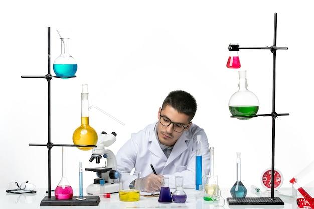 Vue de face chimiste masculin en costume médical assis et rédiger des notes sur fond blanc virus covid splash maladie science