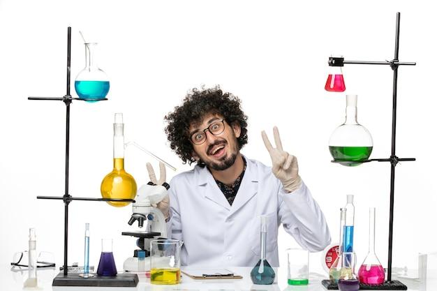 Vue de face chimiste masculin en costume médical assis et souriant sur un bureau blanc