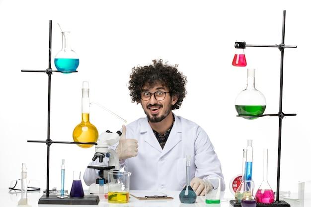 Vue de face chimiste masculin en costume médical assis et souriant sur un espace blanc