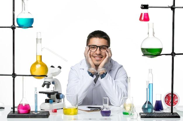 Vue de face chimiste masculin en costume médical assis et souriant sur fond blanc virus covid splash maladie science