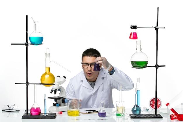 Vue de face chimiste masculin en costume médical assis et tenant le ballon avec une solution violette sur fond blanc virus covid splash maladie science