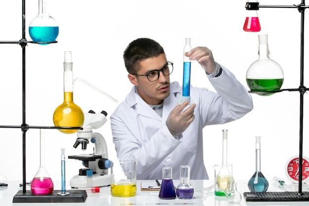 Vue de face chimiste masculin en costume médical assis tenant une solution sur fond blanc virus covid- splash maladie science