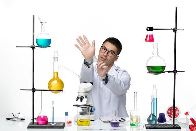Vue de face chimiste masculin en costume médical blanc assis avec différentes solutions sur fond blanc laboratoire de science du virus de la maladie de covid