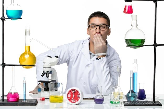 Vue de face chimiste masculin en costume médical blanc assis avec des solutions sur fond blanc virus de laboratoire science pandémie de covid