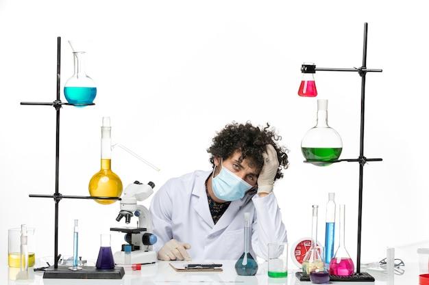 Vue de face chimiste masculin en costume médical blanc et avec masque se sentir fatigué sur l'espace blanc