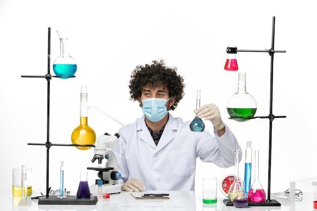 Vue de face chimiste masculin en costume médical blanc et avec masque tenant une solution bleue sur un bureau blanc