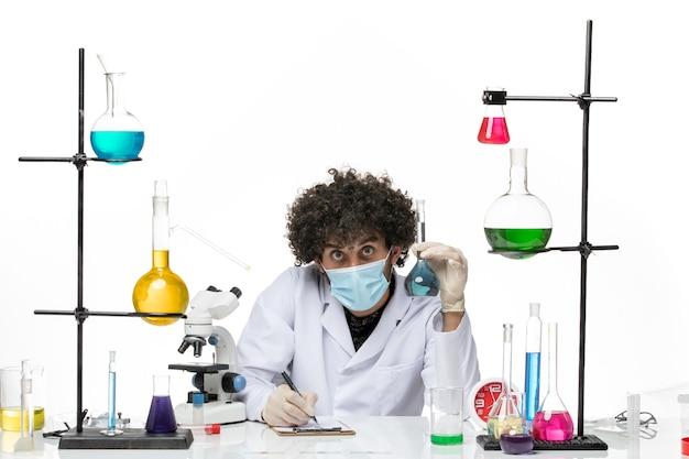Vue de face chimiste masculin en costume médical blanc et avec une solution de maintien de masque écrit sur un espace blanc