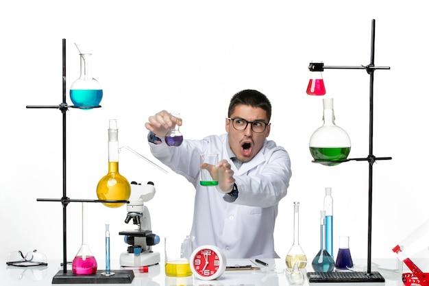 Vue de face chimiste masculin en costume médical blanc tenant des flacons avec des solutions sur fond blanc virus science laboratoire pandémique covid