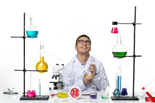 Vue de face chimiste masculin en costume médical blanc travaillant avec des solutions souriant sur fond blanc virus science pandémie de laboratoire covid