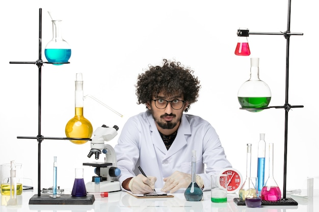 Vue de face chimiste masculin en costume médical écrit des notes sur un bureau blanc