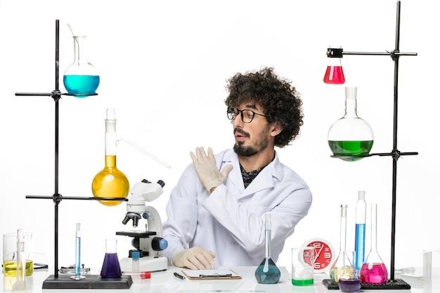 Vue de face chimiste masculin en costume médical fixant son costume sur un espace blanc