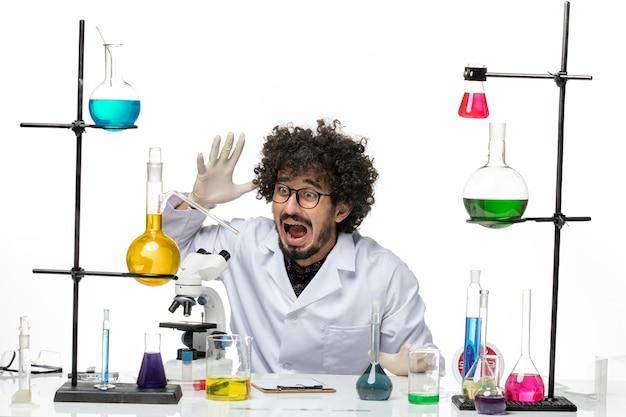 Vue de face chimiste masculin en costume médical juste assis en face de la table avec des solutions sur un bureau blanc