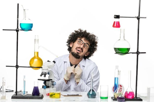 Vue de face chimiste masculin en costume médical juste assis en face de la table avec des solutions sur un espace blanc clair