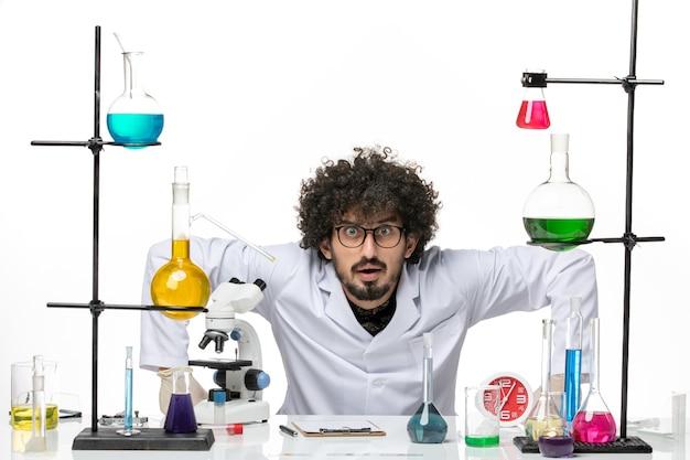 Vue de face chimiste masculin en costume médical juste assis en face de la table avec des solutions sur l'espace blanc