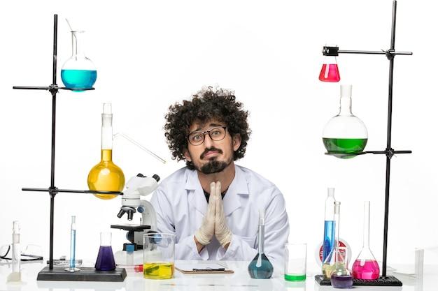 Vue de face chimiste masculin en costume médical juste assis en face de la table avec des solutions priant sur l'espace blanc