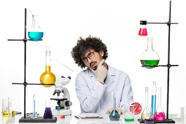 Vue de face chimiste masculin en costume médical juste assis en face de la table avec des solutions de réflexion sur l'espace blanc