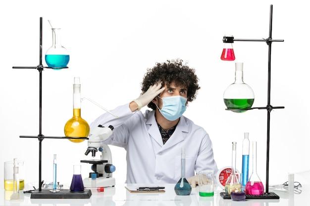 Vue de face chimiste masculin en costume médical et avec masque juste assis avec différentes solutions sur un bureau blanc