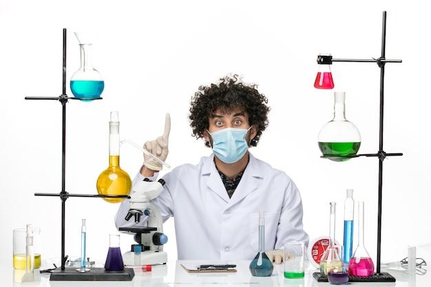 Vue de face chimiste masculin en costume médical et avec masque juste assis avec différentes solutions posant sur un bureau blanc