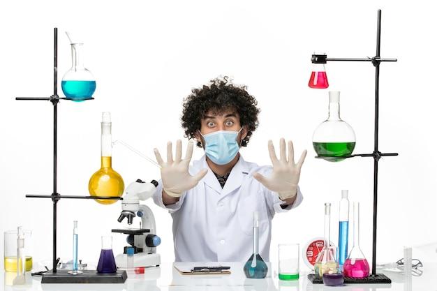 Vue de face chimiste masculin en costume médical et avec masque montrant ses mains sur l'espace blanc