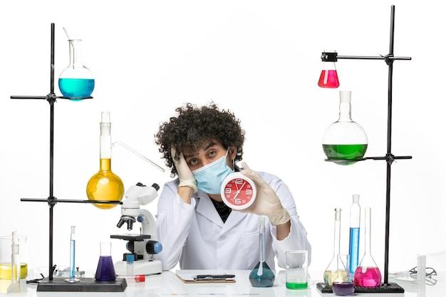 Vue de face chimiste masculin en costume médical et avec un masque tenant une horloge sur un espace blanc clair