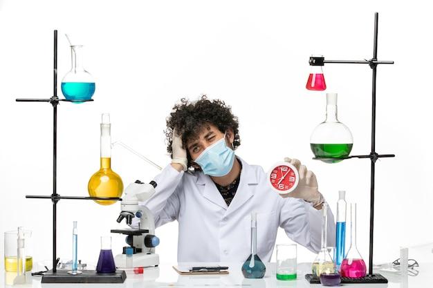 Vue de face chimiste masculin en costume médical et avec masque tenant des horloges rouges sur un bureau blanc