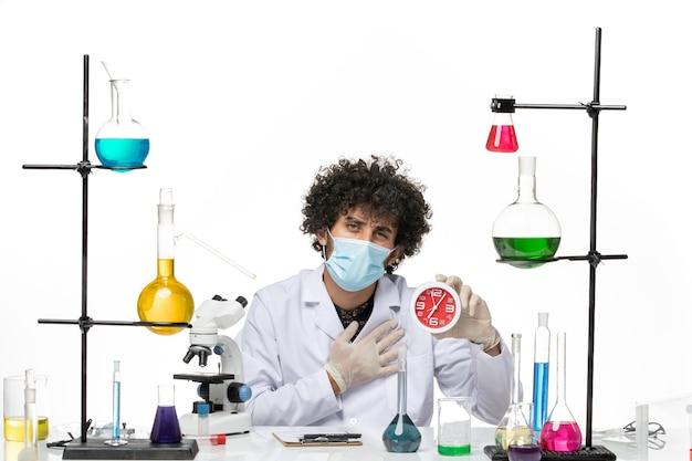 Vue de face chimiste masculin en costume médical et avec masque tenant des horloges rouges sur l'espace blanc