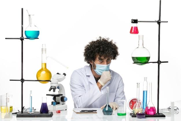 Vue de face chimiste masculin en costume médical et avec masque de toux sur l'espace blanc