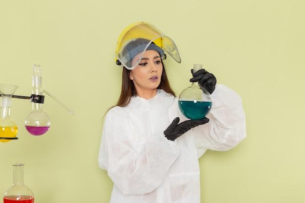Vue de face chimiste en tenue de protection spéciale tenant le ballon avec une solution bleue sur une surface verte