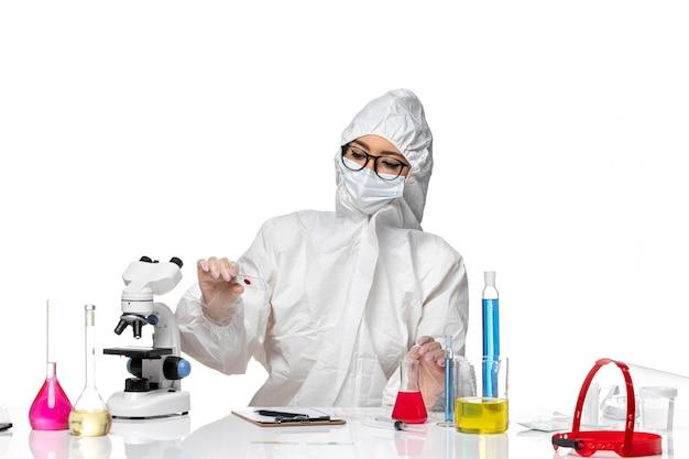 Vue de face chimiste en tenue de protection spéciale tenant un échantillon sur la pandémie de virus covid chimie bureau blanc