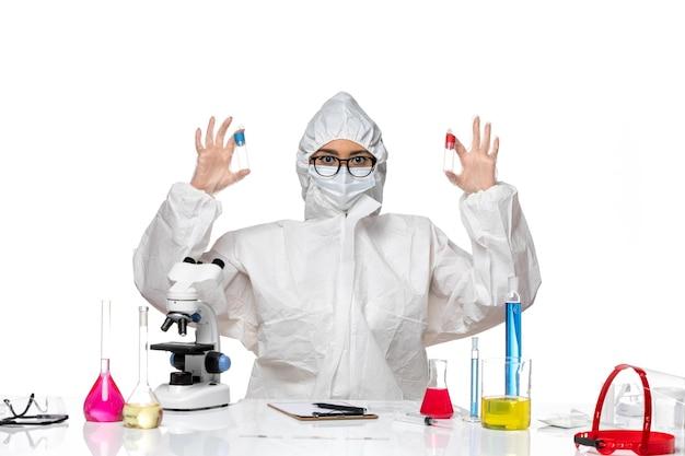 Vue de face chimiste en tenue de protection spéciale tenant des flacons vides sur blanc bureau virus chimie de la santé covid