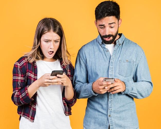 Vue de face choqué couple sur leurs téléphones