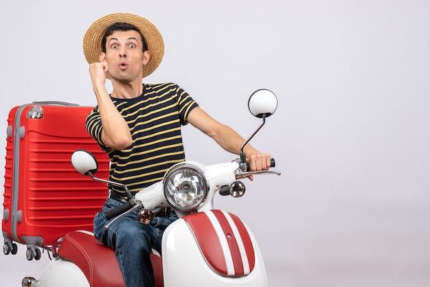 Vue de face choqué jeune homme avec chapeau de paille sur cyclomoteur montrant punch