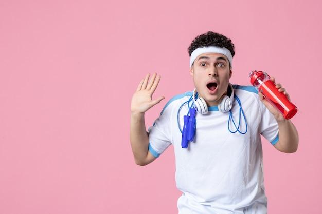 Vue de face choqué jeune homme en vêtements de sport avec corde à sauter et de l'eau