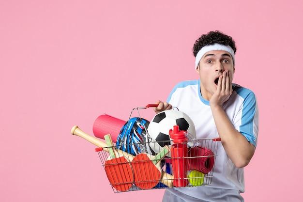 Vue de face choqué jeune homme en vêtements de sport avec panier plein de choses sportives