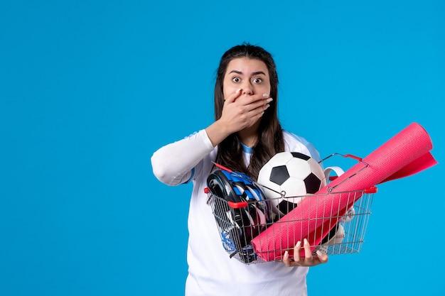 Vue de face choquée jeune femme avec panier plein de choses sportives