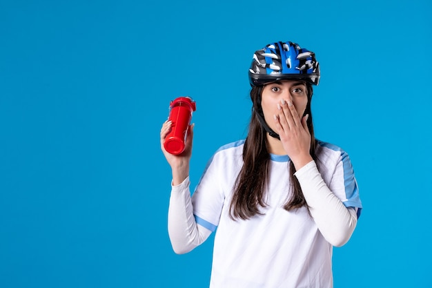Vue de face choquée jeune femme en vêtements de sport et casque