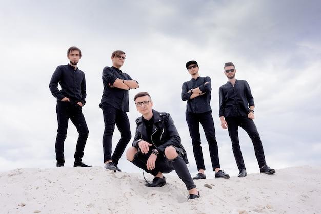 Vue de face de cinq hommes posant sur la colline de sable et regardant la caméra